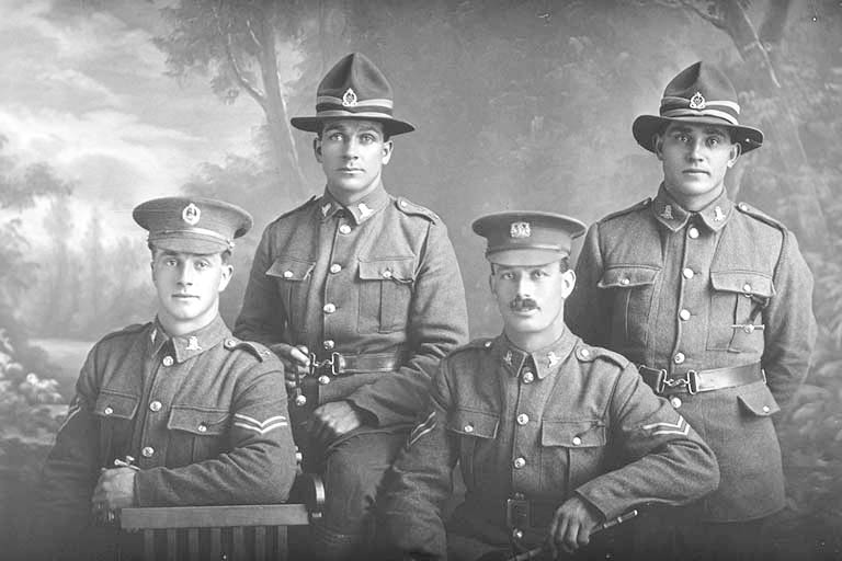 Group portrait of four men, all of the 19th Reinforcements, including on the left is Corporal Henry Archibald Basil Cruller, Reg No 31401, of J Company, killed in action in France on 12 October 1917 at the Battle of Passchendaele. On the right is Private Robert Henry Flavell, Reg No 31407, also of J Company. - Auckland Libraries
