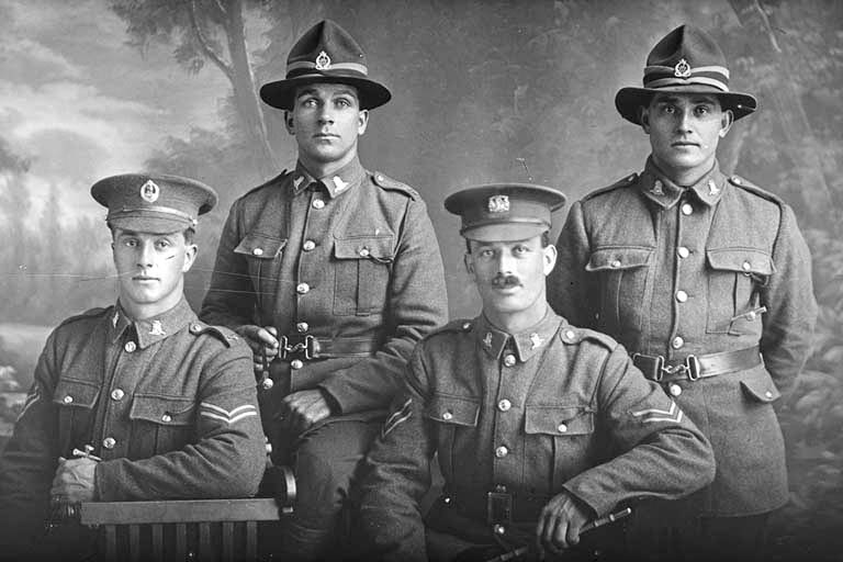 Group portrait of four men, all of the 19th Reinforcements, including, on the left, is Corporal Henry Archibald Basil Cruller, Reg No 31401, of J Company, killed in action in France on 12 October 1917 at the Battle of Passchendaele. On the right is Private Robert Henry Flavell, Reg No 31407, also of J Company. - Auckland Libraries
