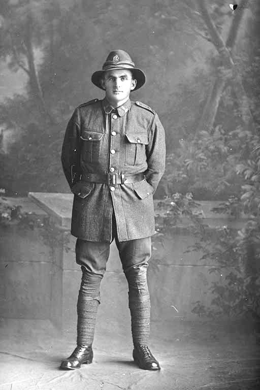Full length portrait of Rifleman Olds of the New Zealand Rifle Brigade, possibly Harold Olds, Reg No 46478, J Company. Killed in action in France on 12 October 1917 at the Battle of Passchendaele. - Auckland Libraries