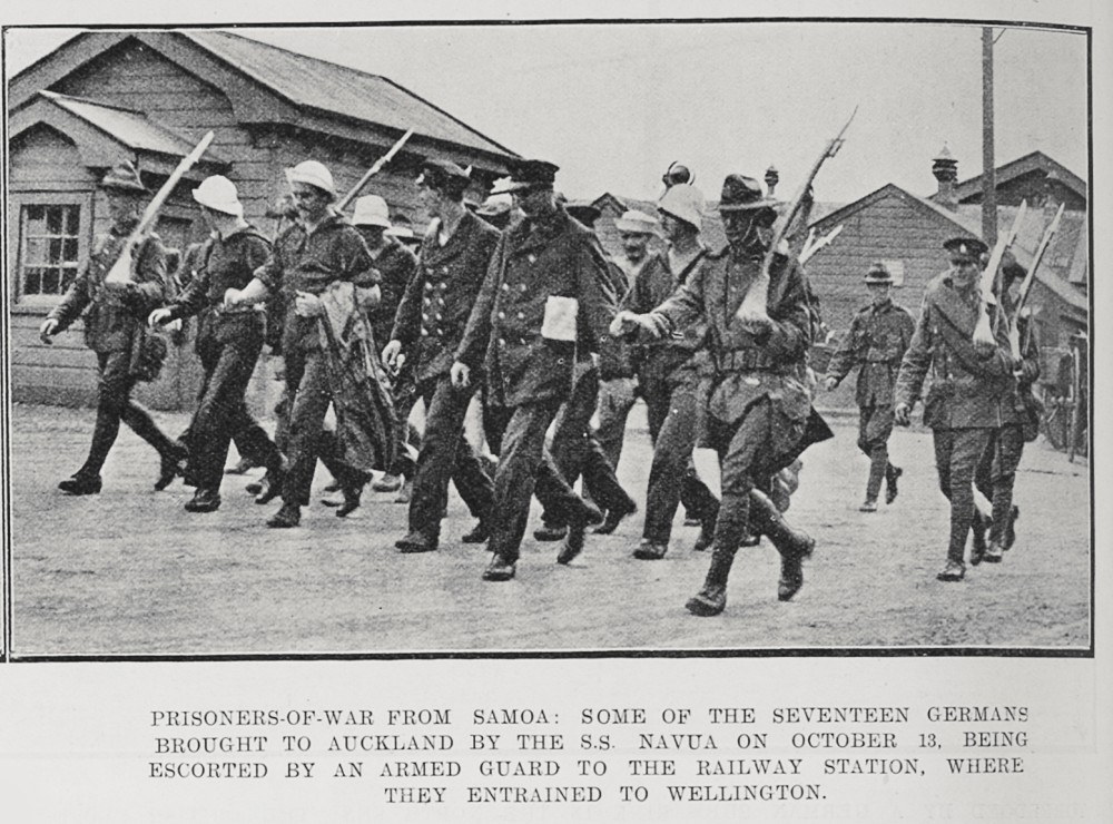 Prisoners-of-war from Samoa: Some of the seventeen Germans brought to Auckland by the S S Navua on October 13, being escorted by an armed guard to the railway station, where they entrained to Wellington. - Auckland Libraries