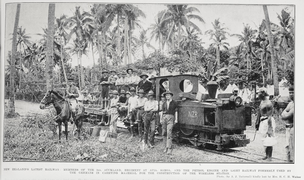 New Zealand's latest railway: Members of the 3rd, Auckland Regiment at Apia, Samoa, and the petrol engine and light railway formerly used by the Germans in carrying material for the construction of the wireless station. - Auckland Libraries