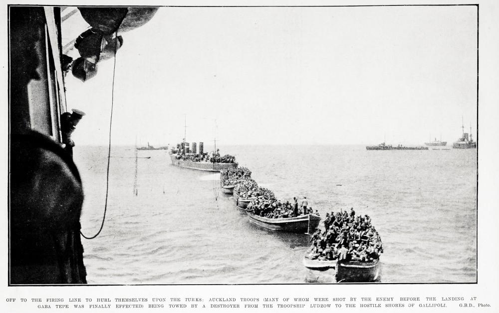 Off to the firing line to hurl themselves upon the Turks: Auckland troops (many of whom were shot by the enemy before the landing at Gaba Tepe was finally effected) being towed by a destroyer from the troopship Ludzow to the hostile shores of Gallipoli. - Auckland Libraries
