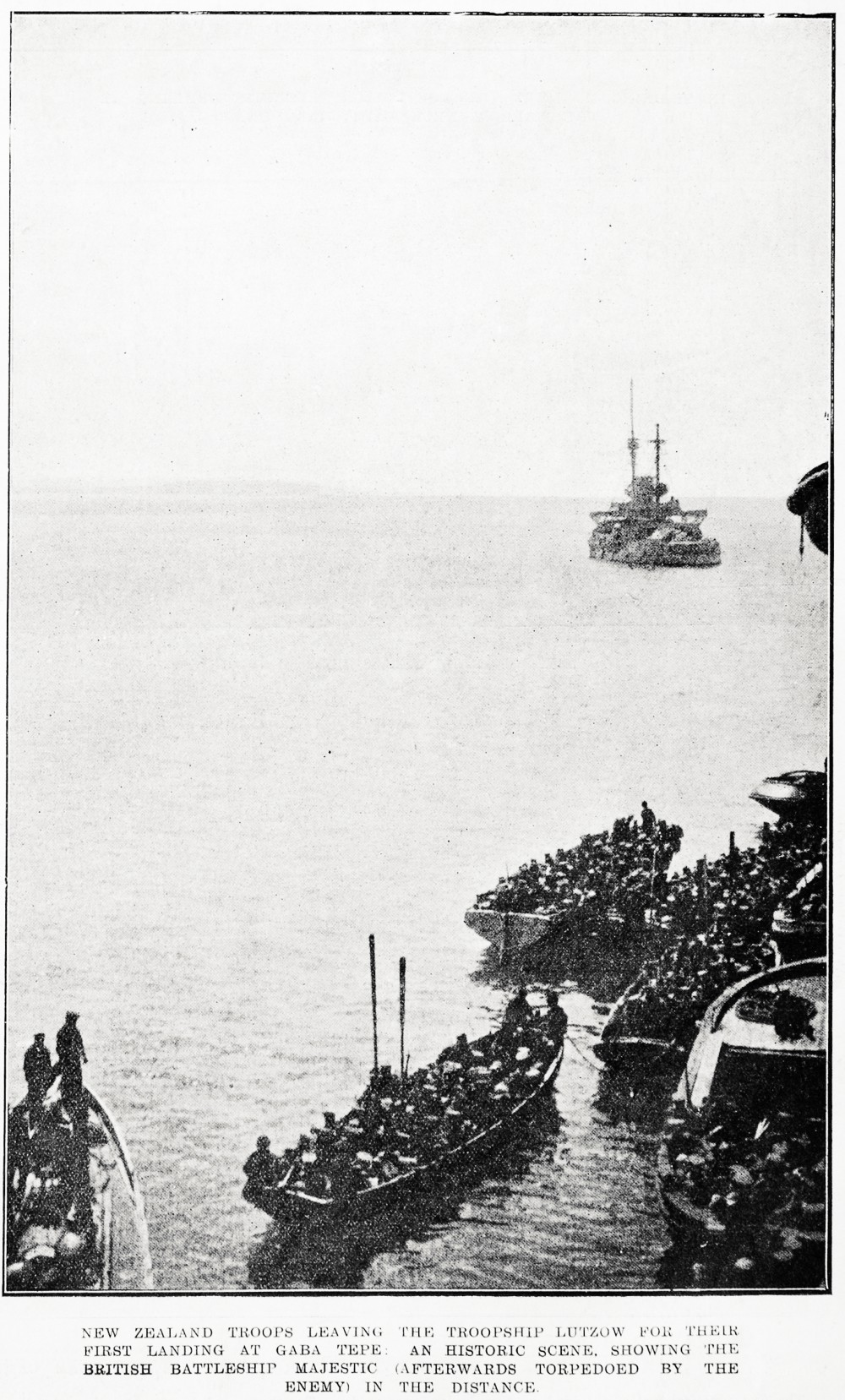 New Zealand troops leaving the troopship Lutzow for their first landing at Gaba Tepe: an historic scene. Showing the British battleship Majestic (afterwards torpedoed by the enemy) in the distance. - Auckland Libraries