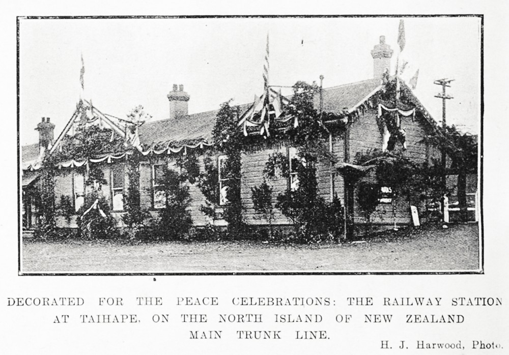 Decorated for the peace celebrations: the railway station at Taihape, on the North Island of New Zealand main trunk line. - Auckland Libraries