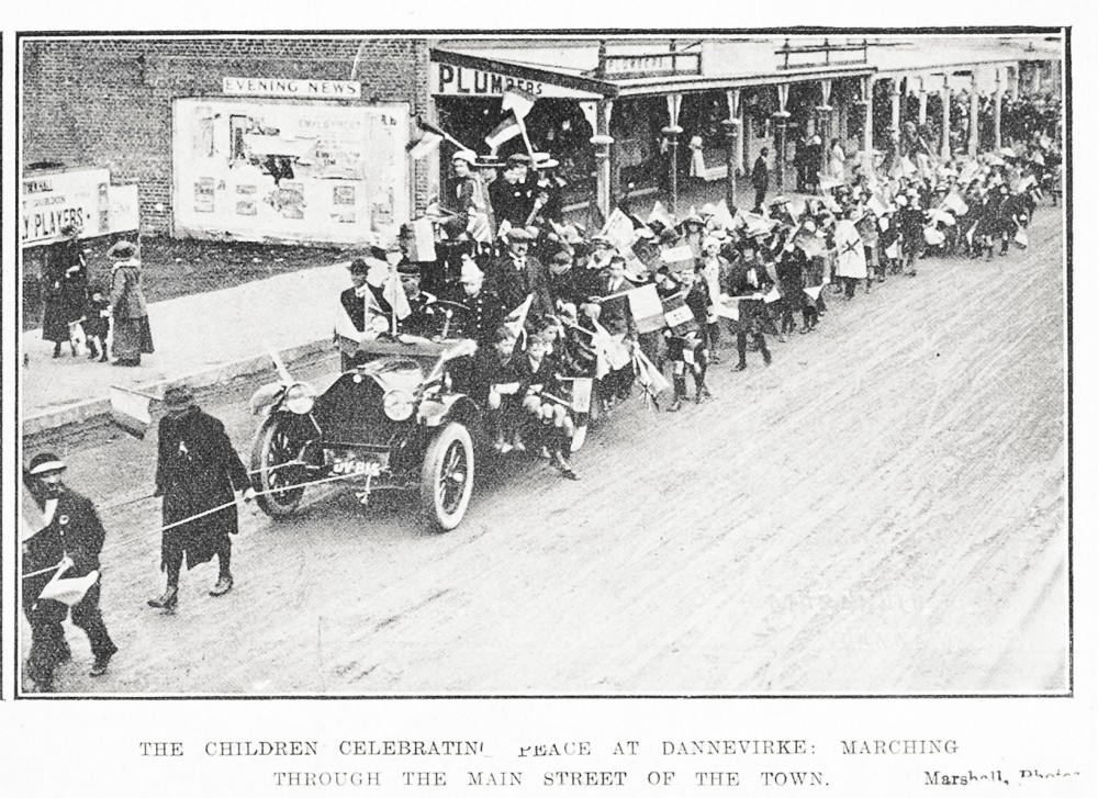 The children celebrating peace at Dannevirke: marching through the main street of the town. - Auckland Libraries