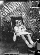 Showing a young girl seated in a deck chair, taken...